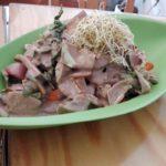 Klassisches Chop-Suey mit frischem Bio-Wok-Gemüse und Kohlrabinudeln serviert auf einem grünen Bambusteller im veganen Restaurant Mei Wok in Köln.