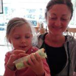 Unsere Tochter Romy sitzt freudestrahlend mit einem Rohkost-Wrap auf dem Schoß ihrer Mutter.