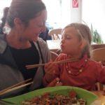 Meine Tochter Romy und meine Frau Doris essen zusammen mit Stäbchen ein rohveganes asiatisches Gericht im Restaurant Mei Wok in Köln.