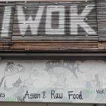 """Ein großes rechteckiges Schild aus runden, braunen Bambushölzern mit der weißen Beschriftung """"MEIWOK"""". Neben der Beschriftung befindet sich eine grüne Blume in einem weißen Kreis, deren zwei Blätter eine V-Form bilden. Unter dem Schild ist die Außenwand künstlerisch mit verschiedenen Figuren schwarz und weiß gezeichnet. Und darauf befindet sich die Beschriftung """"MeiWok"""" """"Green Smoothies"""" Mei Wok""""Asian & Raw Food"""" """"Welcom to Mei Wok"""". Bis auf das """"Mei"""" (in grüner Schrift) ist die Beschriftung schwarz."""