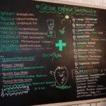 Eine große, schwarze Tafel mit grüner, roter und weißer Beschriftung mit allen Smoothiekombinationen aus dem veganen Restaurant Mei Wok in Köln.