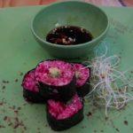 Vier rohvegane Sushi serviert mit einer scharfen Tamarisoße auf einem grünen Bambusteller mit Alfalfasprossen garniert