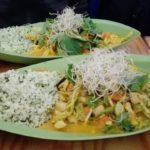 2 Würzig scharfe thailändische Tom Yum mit Bio-Wok-Gemüse und Blumenkohlreis serviert auf zwei grüne Bambusteller im veganen Restaurant MeiWok in Köln.
