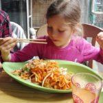 Unsere Tochter Romy im veganen Restaurant Mei Wok in Köln sitzt an einem Tisch und isst mit Stäbchen rohe Karottennudeln mit Bio-Wok-Gemüse.