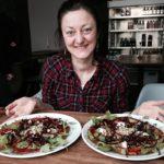 Doris sitzt mit ausgebreiteten Armen vor 2 Pizzen im Rohkostrestaurant Rawtastic in Berlin.