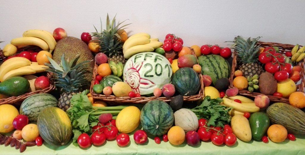 Ein Tisch mit hellgrüner Tischdecke. Der Tisch ist komplett mit verschiedenen Südfrüchten wie Melonen, Ananas, Zitrusfrüchte, Bananen sowie rote Äpfel, Tomaten und Staudensellerie dekoriert. In der Mitte befindet sich eine Wassermelone, bei der die Schale so entfernt wurde, dass nur noch FFF 2017 stehen geblieben ist. Außerdem ist noch eine lachende Sonne eingeritzt.