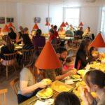 Ca. 50 Personen sitzen an einer u-förmigen Tischreihe und essen gemeinsam Früchte.
