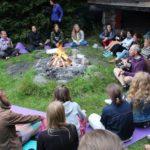 Eine Gruppe von ca. 30 Personen sitzen um ein Lagerfeuer. Ronnie spielt Lieder auf seiner Gitarre.