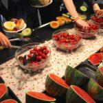 Verschiedene Melonensorten rings auf dem Buffettisch verteilt und in der Mitte sind große Schüsseln gefüllt mit frischen Erdbeeren.