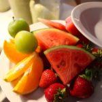 Obstteller mit Wassermelonenscheiben, Orangenstücke, Erdbeeren und Mirabellen