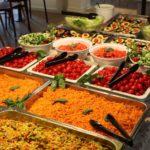 Salatbuffet mit Gurken, Karotten, Tomaten, geschnittenen Eisbergsalat und halbierte Avocados mit einer Datteltomate in der Mitte