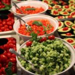 Salatbuffet mit Gurken, Karotten, Tomaten und halbierte Avocados mit einer Datteltomate in der Mitte